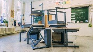 Banken staan rommelig op elkaar gestapeld in een klaslokaal