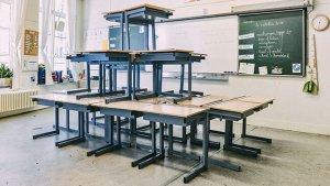 Banken staan netjes op elkaar gestapeld in een klaslokaal