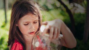 Meisje kijkt naar plastieken fles