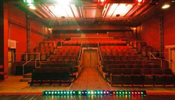Een theaterzaal met rode stoelen bekeken vanaf het podium