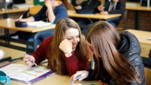 Twee meisjes praten in de klas