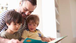 Vader en twee zoontjes lezen samen een boek