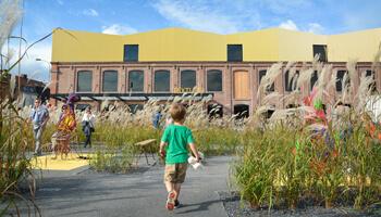 Jongen wandelt door tuin met vlasplanten met op de achtergrond het gebouw van Texture, museum over Leie en vlas