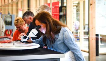 Vrouw kijkt door microscoop