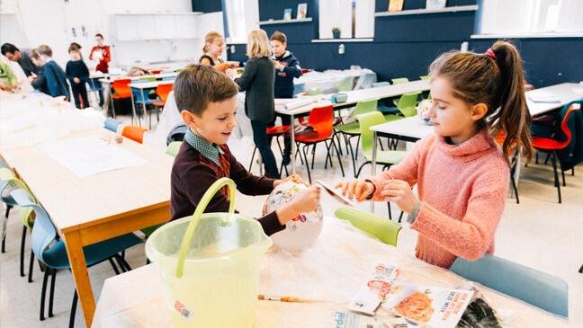 jongen en meisje werken met papier maché