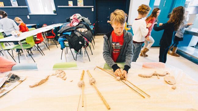 jongen maakt skelet met klei en hout