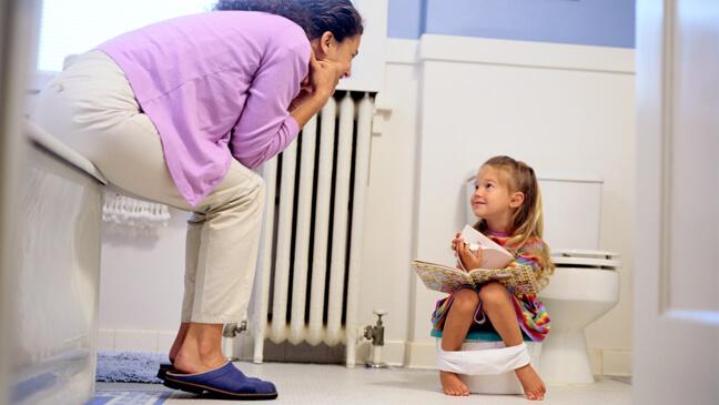 Mama met kleutermeisje op badkamer terwijl meisje op potje zit