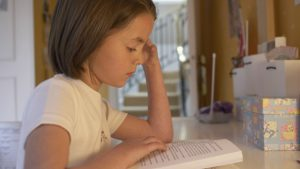 meisje leest boek aan bureau