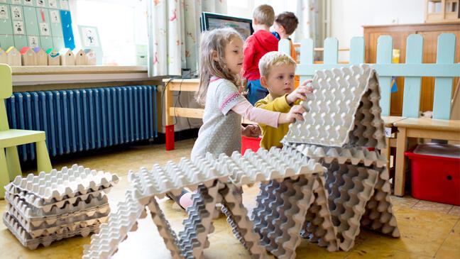 Kleuters bouwen toren met eierdozen