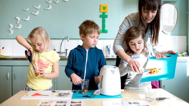 Juf Lieselot helpt kleuters bij het kleuren van water