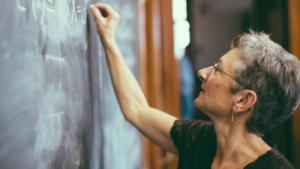 Vrouwelijke leraar schrijft formule in krijt op bord