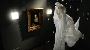 Jurk hangt op met schilderij op de achtergrond
