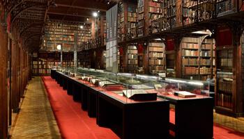 Oude boeken op een tafel omringd door boekenkasten