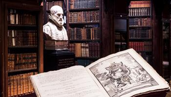 Een open boek met een buste op de achtergrond, omringd door boekenkasten