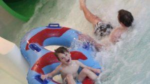 kinderen glijden uit wildwaterglijbaan
