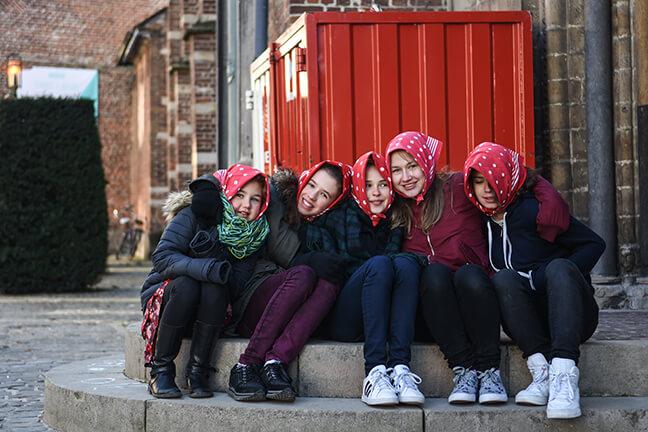 5 meisjes zitten op een stoep