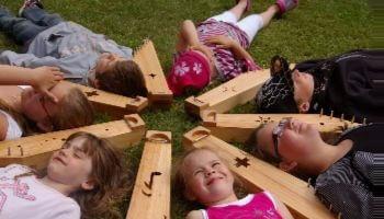 Kinderen ligen in cirkel tussen muziekinstrumenten op het gras