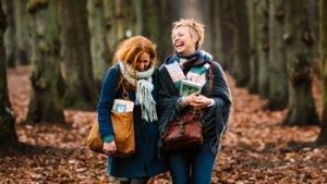 twee vrouwen met een boek in het bos