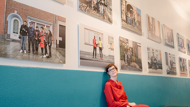 Katrien Demaeght in de gang van de school met het fotoproject aan de muren