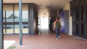 Jongen wandelt naar buiten met rugzak