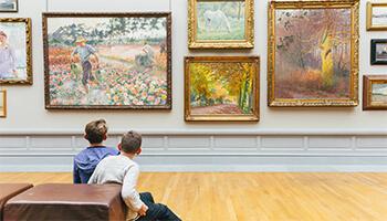 2 jongens kijken naar schilderijen