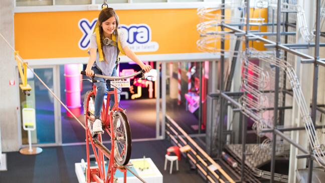 Meisje met fiets op koord in Technopolis