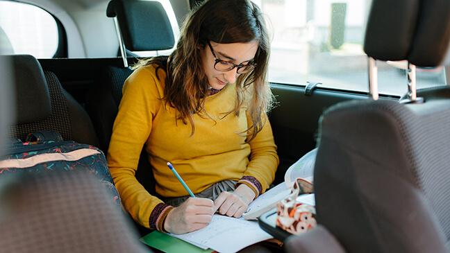 meisje doet huiswerk in wagen