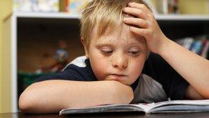 Jongen met downsyndroom aan het lezen