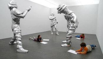 kinderen liggen tussen levensgrote beeldhouwwerken in het museum