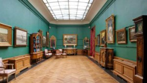 zaal in museum met schilderijen en meubels