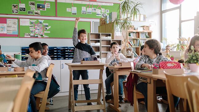 jongen aan een statafel in de klas