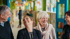 4 personen lachen naar elkaar in de gang van een school