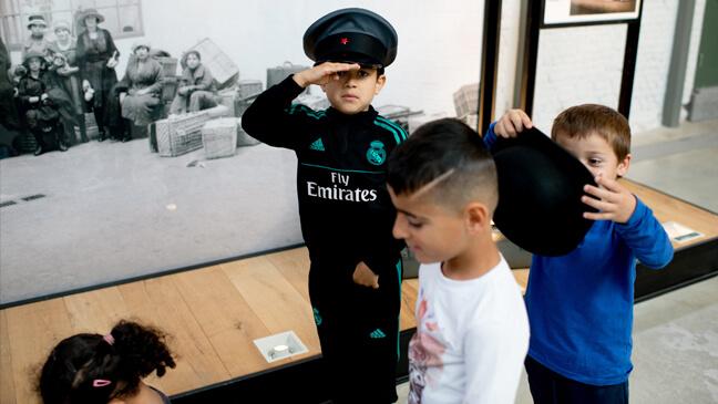 Red Starline Antwerpen: Kleuters dragen de hoofddeksels die ze op de foto aan de ingang zien.