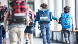 Kinderen met rugzak rennen door schoolgang
