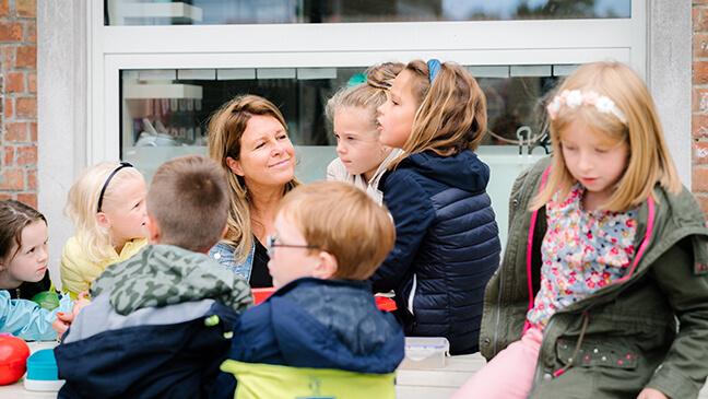 directeur Rebekka Buyse tussen haar leerlingen op de speelplaats