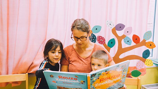 Juf Hanne leest boek met 2 leerlingen