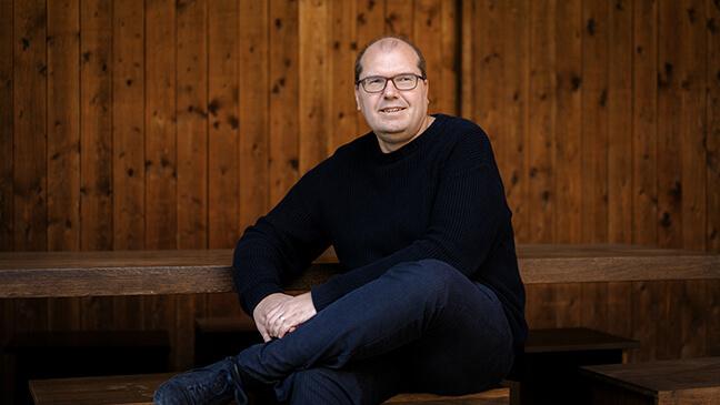 Architect Dimitri Minten zit op een bank.