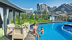 Vrouw aan zwembad van hotel met gebouwen op achtergrond