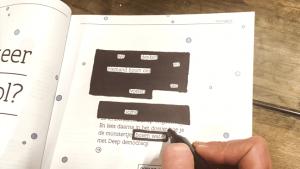 Een hand doorhaalt woorden met een zwarte stift in een magazine