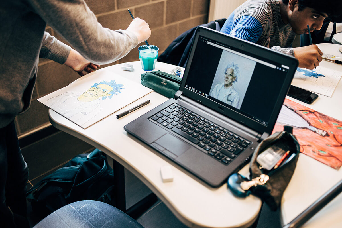 Een leerling gebruikt een laptop van de school.