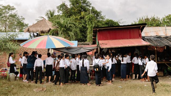 Cambodja: Leerlingen schuiven aan bij kraampjes op de speelplaats