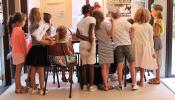 kinderen kijken naar een project rond een tafel
