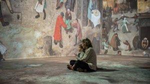 moeder met kind tussen projectie van schilderij van Bruegel