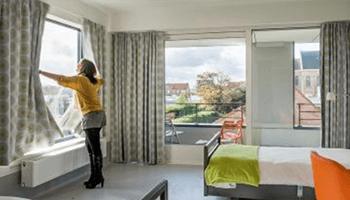 Vrouw opent gordijnen in hotelkamer