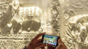Muursculpturen vergelijken met origineel schilderij via app in smartphone