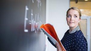 Jonge leraar schrijft op schoolbord