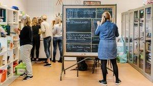 leraar aan een planningsbord, toont dat jobcrafting of een jobruilbeurs passen in het personeelsbeleid van een school
