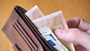Mannelijke hand neem eurobiljetten uit portefeuille