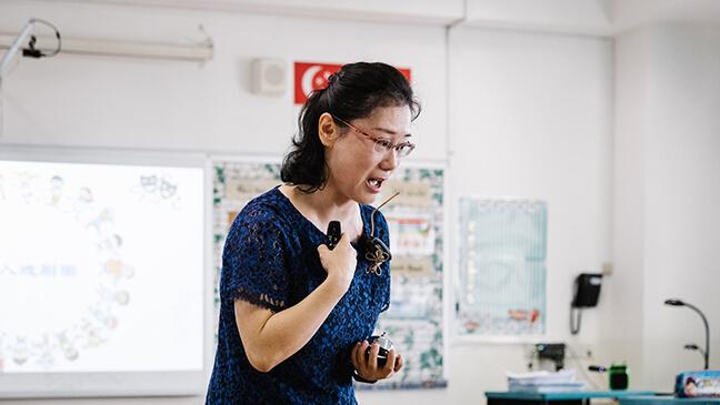 leraar Dai Ping met een microfoon in de klas