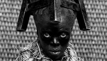 zwarte man met tabouret op zijn hoofd